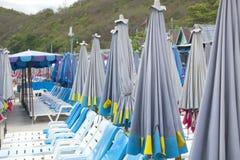 Klappstühle und Regenschirme auf dem Strand Stockfotografie