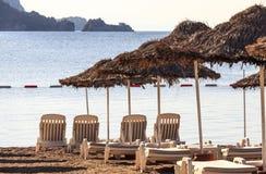 Klappstühle und Regenschirme auf Strand stockfoto