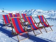 Klappstühle vor Ski neigt sich in Alpenberge Stockbilder