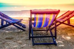 Klappstuhl mit blauer Farbe auf dem Strand im Sonnenlicht mit Meeransicht/Natur und Feiertage Lizenzfreies Stockbild