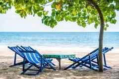 Klappstuhl mit blauer Farbe auf dem Strand im Sonnenlicht mit Meeransicht/Natur und Feiertage Lizenzfreie Stockbilder