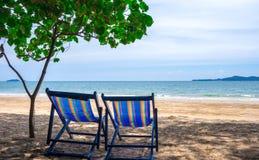 Klappstuhl mit blauer Farbe auf dem Strand im Sonnenlicht mit Meeransicht/Natur und Feiertage Stockbild