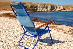 Klappstuhl steht auf dem Strand, dem Konzept von Ferien und Reise lizenzfreies stockfoto