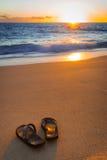 Klapy (kapcie) na tropikalnej plaży przy zmierzchem zdjęcie royalty free