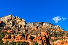 Klar farbiger, felsiger Abhang in Sedona, Arizona Rechter roter Sandstein mit tiefem blauem Himmel und weißer Wolke im Hintergrun lizenzfreie stockbilder