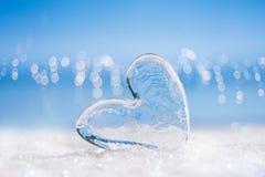 Klar glass hjärta på vit blänker och slösar bakgrund royaltyfri foto