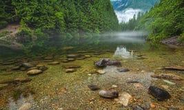 Klar Lake med Rocks och mist i avstånd Arkivbild