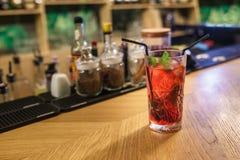 Klar röd alkoholcoctail på bakgrundsstänger av kryddor i en elitstång för framställning coctailar av den kanelbruna nyponkryddnej royaltyfri bild