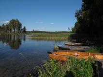 Klar sjö med ett fartyg på kusten Royaltyfria Bilder