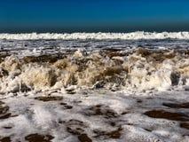 Klara blåa himlar och solljus med Atlantic Ocean vågor som kraschar på sandstranden med inga personer i Agadir, Marocko, Afrika arkivbild