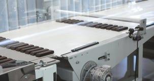 Klara choklader på produktionslinjen på linjen för chokladfabrikstillverkning av söt mat för chokladgodis på arkivfilmer