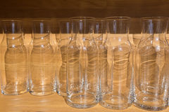 Klara tomma glasflaskor eller tillbringare på den wood tabellen Arkivbild