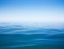 Klare Himmel- und Wasseroberfläche des ruhigen Sees oder des Ozeans Stockfotografie