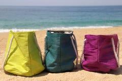 Klare mehrfarbige Strandtaschen auf der Küste Lizenzfreies Stockfoto