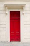 Klare rote Tür auf einer weißen Wand Lizenzfreies Stockfoto