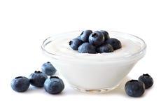 Klare Schüssel Jogurt mit Blaubeeren über Weiß Stockfoto