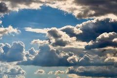 Klare und drastische Wolken mit dem blauen Himmel, der durch glänzt Stockbild