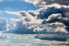 Klare und drastische Wolken mit dem blauen Himmel, der durch glänzt Lizenzfreies Stockbild