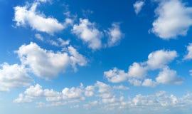 Klarer blauer Himmel mit weißen flaumigen Wolken Feld des grünen Grases gegen einen blauen Himmel mit wispy weißen Wolken stockfotografie