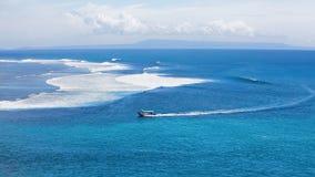 Klarer blauer Ozean mit Boot und Surfern auf großen Wellen Stockfoto