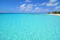 Klarer blauer tropischer Ozean mit weißem Sandstrand im Hintergrund Lizenzfreie Stockfotos