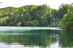 Klarer grüner See mit Wasserfällen Stockfoto