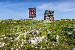 Klarer Trem-Gipfelstein und -Wegweiser auf trockenem Berg in Serbien Lizenzfreies Stockfoto