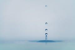 Klarer Tropfen des blauen Wassers mit Kräuselung auf Oberfläche Stockfoto