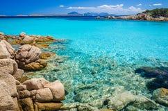 Klares erstaunliches Azurblau färbte Meerwasser mit gtanote Felsen in Capriccioli-Strand, Sardinien, Italien stockbild