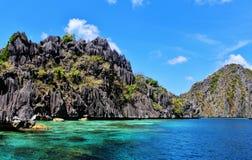 Klares Meerwasser, schwarzer Felsenhügel, Sonnenschein Stockbild
