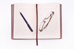 Klares Notizbuch, Gläser und Bücher auf Tabelle Lizenzfreies Stockbild