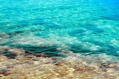 Klares transparentes blaues Meerwasser mit Sand und Steinen Lizenzfreies Stockfoto