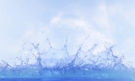 Klares Wasser, das gegen blauen Himmel, weiße Tageslichtwolke spritzt stockfoto