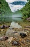 Klares Wasser mit nebelhaftem Berg Stockfoto