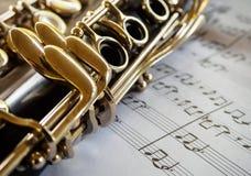 klarinett och ark av musik på träbakgrund Arkivbilder
