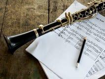 klarinett och ark av musik på träbakgrund Arkivfoton