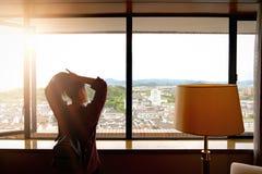 Klart åtsittande hår för kvinna, medan se sikt från fönster arkivbild