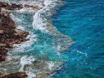 Klart blått hav på kanten av steniga kuster royaltyfria bilder