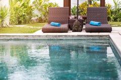 Klart blått vatten i simbassäng och sunbeds Arkivfoto