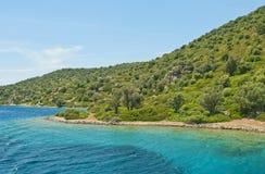 Klart blått vatten på den gröna bergiga ön Arkivbilder
