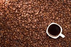 klart bruk för bakgrundskaffe Kaffebönor och kopp kaffe över tabellen Royaltyfri Bild