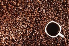 klart bruk för bakgrundskaffe Kaffebönor och kopp kaffe över tabellen Arkivbilder