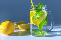Klart exponeringsglas rånar fyllt med vatten, den skivade citronen för ‹för †och mintkaramellsidor med gult sugrör som tänds arkivbilder