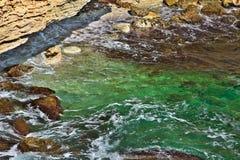 Klart havssemesterortvatten med härlig naturlig bakgrund för stenar Royaltyfri Bild