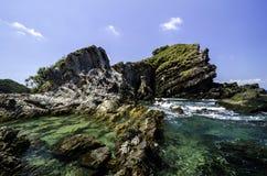 Klart havsvatten omgav den steniga ön med bakgrund för blå himmel på den soliga dagen Arkivfoto