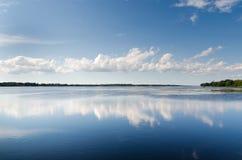 Klart sjölandskap med blå himmel Arkivbild