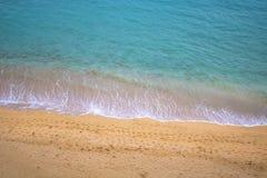 Klart turkoshavvatten med sand och fotspår Royaltyfria Foton