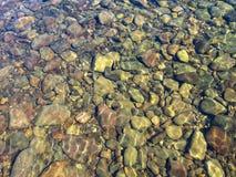 Klart vatten av en bergflod Solilsken blick på flodstenar under klart vatten Arkivbilder