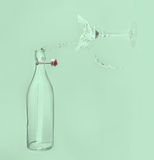 Klart vatten häller horisontal ut ur flaskfärgstänk in i exponeringsglas med Royaltyfria Foton