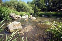 Klart vatten i den snabba lilla floden kör snabbt mellan stenar Arkivfoto